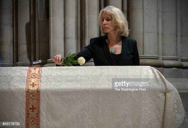 Widow Sally Quinn places a single rose on her husbands casket during funeral services for the late Ben Bradlee former Editor of the Washington Post...