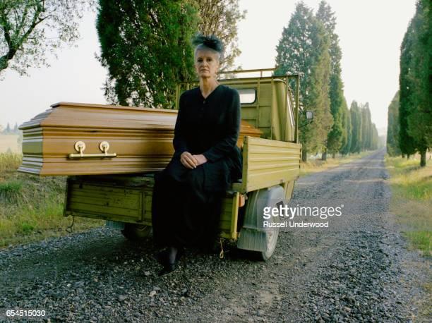 Widow Sitting Next to Coffin in Truck