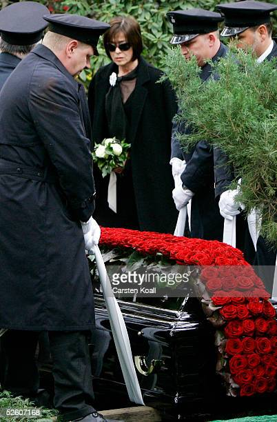 Widow Susanne Juhnke watches pallbearers lower the coffin of the late German actor Harald Juhnke into his grave at funeral services at the...
