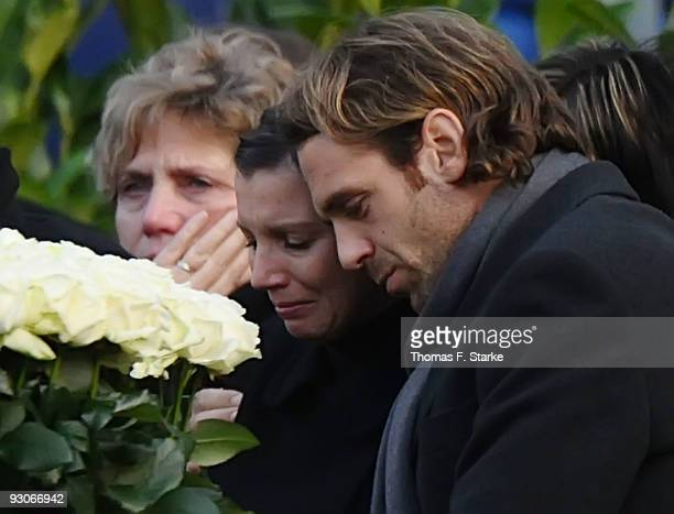 Widow Teresa Enke cries next to Jacques Gassmann during the memorial service prior to Robert Enke's funeral at AWD Arena on November 15 2009 in...