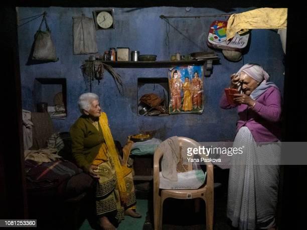 Widow Tulsi Devi watches her sister Chitra Rekha Mata fix her Hindu religious paint at Pashupatinath Ashram in Varanasi India on January 06 2019 The...