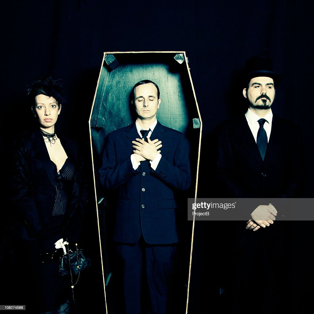 Widow, undertaker and man in coffin : Stock Photo