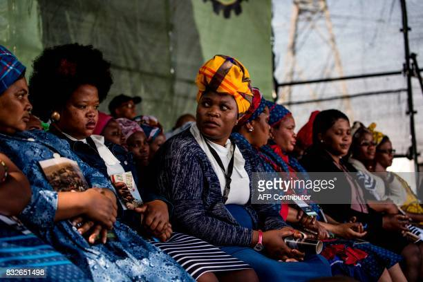 Widows of the deceased striking miners who were killed during the Marikana massacre sit on stage as members of the Association of Mineworkers and the...