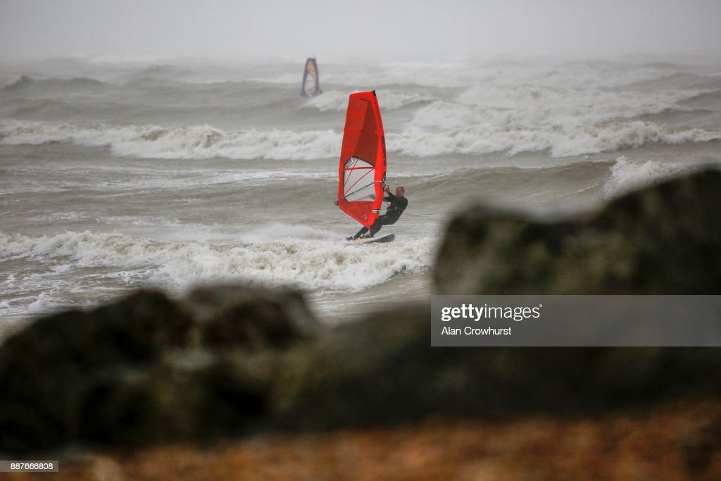 Widsurfers and kitesurfers take advantage of the storm force winds off the coast of West Sussex on December 7, 2017 in Goring, England. Storm Caroline is expected to batter the UK with gusts of up to 90mph and poses a potential risk to life, according to the Met Office.