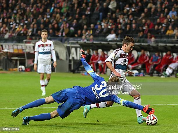Wiedwald of Eintracht Frankfurt in action against his opponent during the Bundesliga soccer match between Eintracht Frankfurt and Bayern München at...