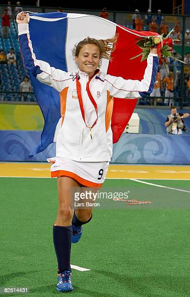 Wieke Dijkstra of the Netherland runs with her countries flag after winning the gold medal in the women's hockey at the Olympic Green Hockey Field on...