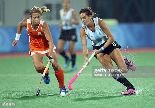 Wieke Dijkstra of The Netherlands vies for the ball with Luciyana Aimar of Argentina during their women's field hockey semifinal match of the 2008...
