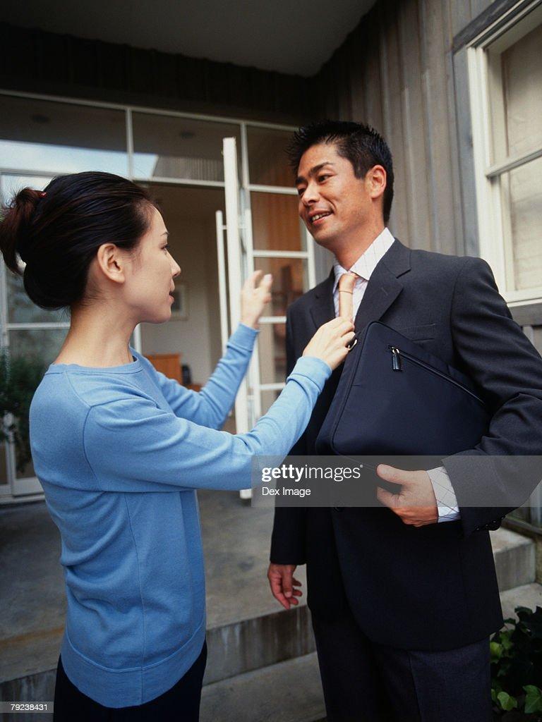 Wife adjusting husband's tie : Stock Photo