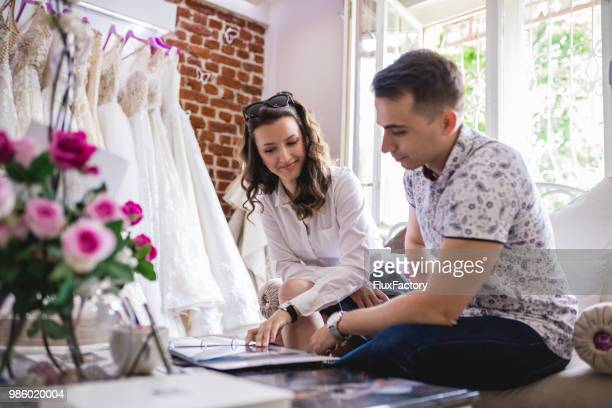 wife and a husband to be looking at the wedding catalog - moment collection stock pictures, royalty-free photos & images