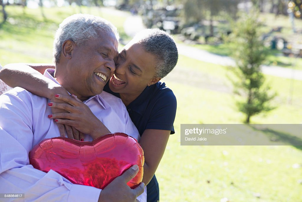 Wife and husband with red heart-shaped balloon, Hahn Park, Los Angeles, California, USA : Stock Photo