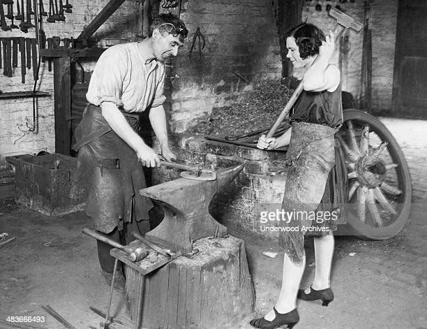 A wife at work as a striker with her husband in their blacksmith shop Wolverhampton England 1930