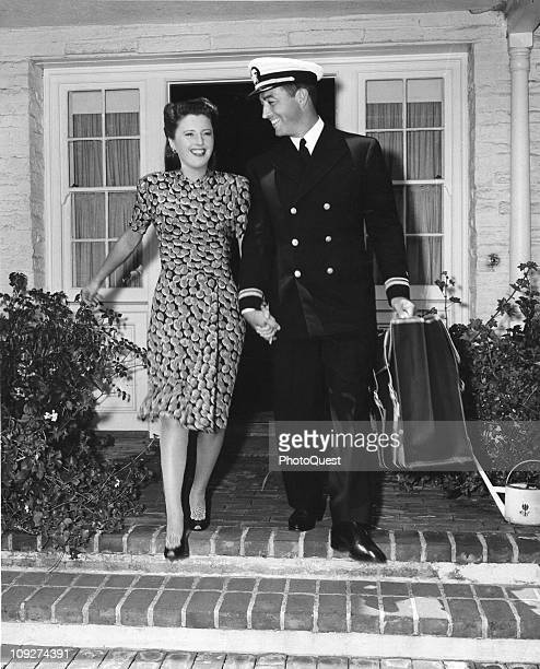 Wife Barbara Stanwyck walks with Lieutenant Robert Taylor to the car as the screen star leaves for active Navy duty ca 1940s
