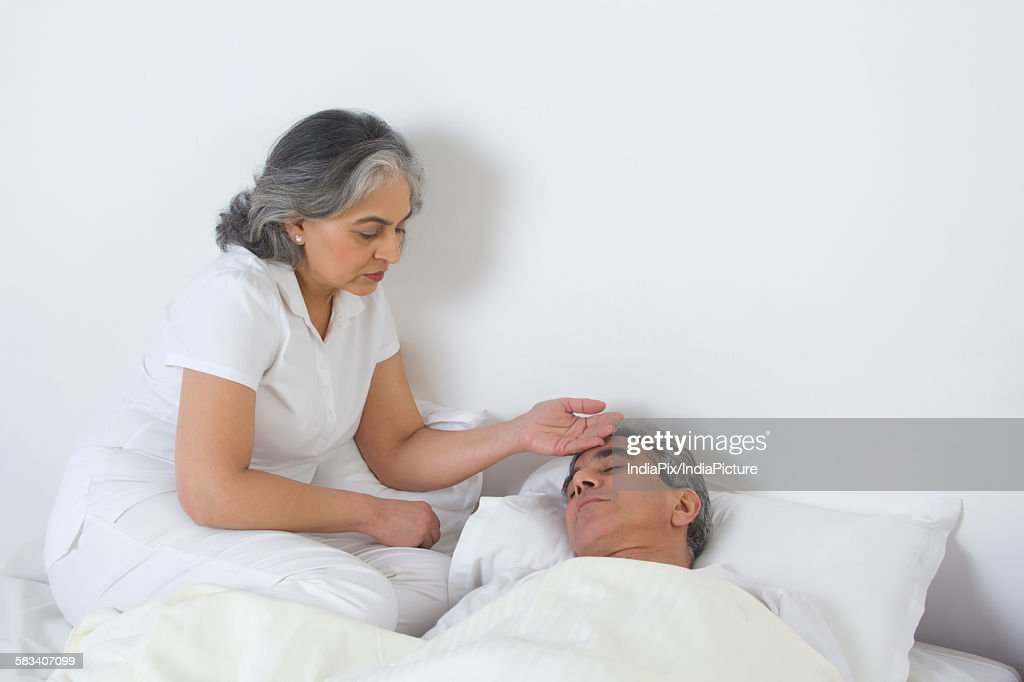 Wife checking husbands fever : Stock Photo