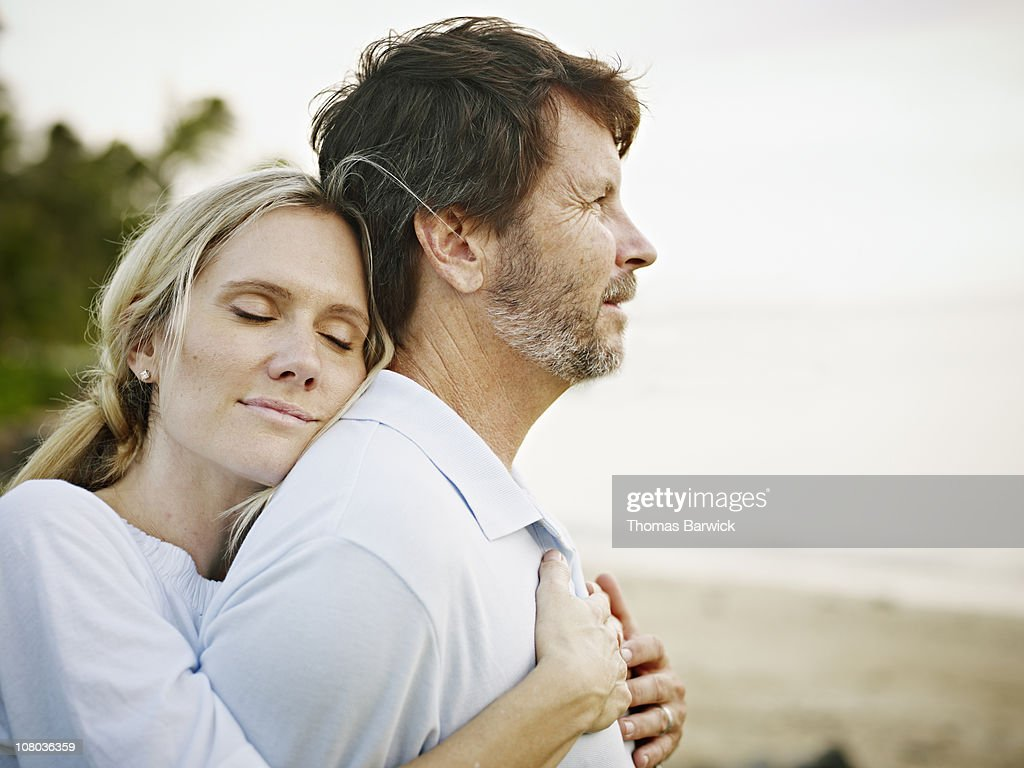 Wife embracing husband on beach at sunset : Stock Photo