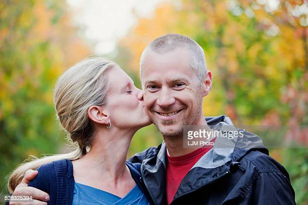Wife Gives Husband A Kiss On The Cheek While Walking Down A Park Path In Autumn; Edmonton Alberta Canada