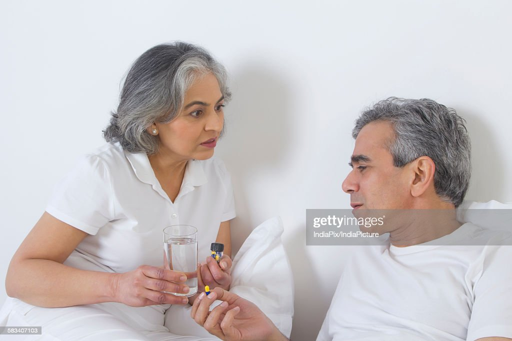 Wife giving medication to husband : Stock Photo