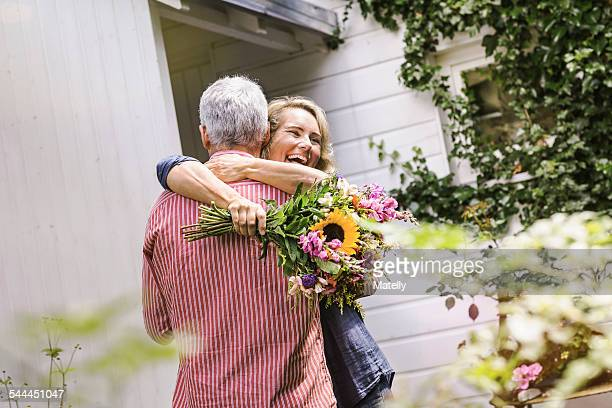 Wife holding bunch of flowers and hugging husband