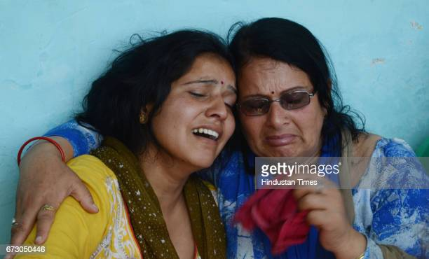 Wife Kiran with martyr CRPF jawan Surender Kumar's body at native village Ner Chowk before cremation on April 25 2017 in Mandi India