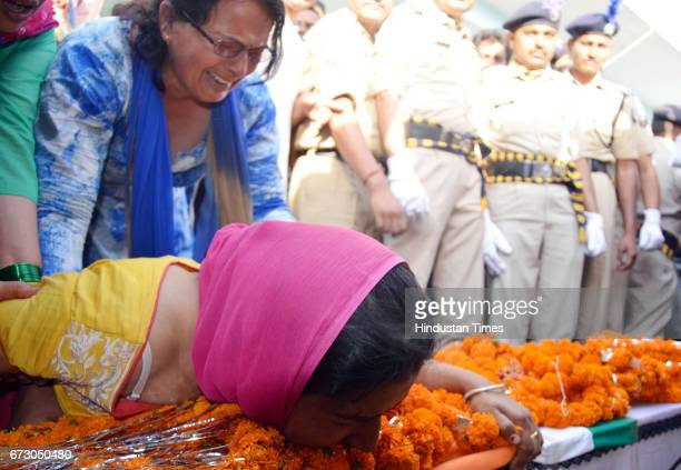 Wife Kiran with martyr CRPF jawan Surender Kumar's body at native village Ner Chowk on April 25 2017 in Mandi India