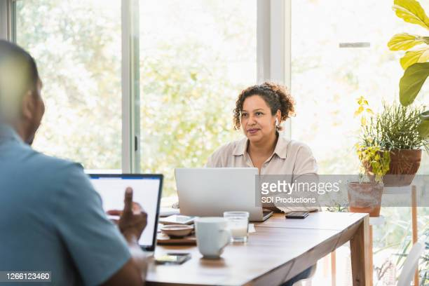 wife listens to husband as they work from home - mid adult couple stock pictures, royalty-free photos & images