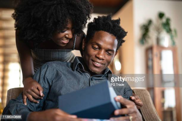 wife making a surprise giving a present to her husband at home - birthday present stock pictures, royalty-free photos & images