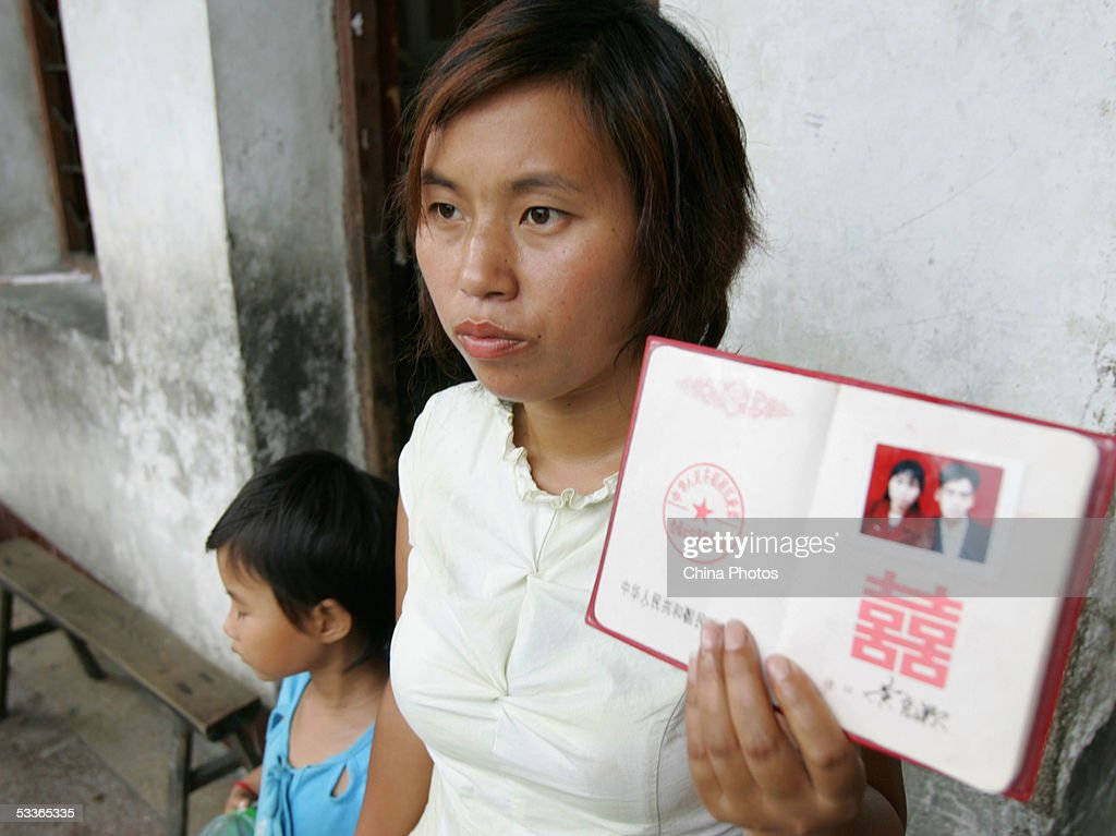 A wife of a missing miner displays her marriage certificate as she waits for her husband's news at the Daxing Colliery where a flood trapped over 100 miners August 9, 2005 in Xingning of Guangdong province, south China. A national investigation team was officially set up by the Chinese State Council on August 11 to find the cause of the accident, as rescuers are still rushing to pump water and search for trapped miners in the pit. The first miners body was found on August 10 with 122 workers still missing and feared dead after being trapped underground for more than five days, officials said, according to state media.