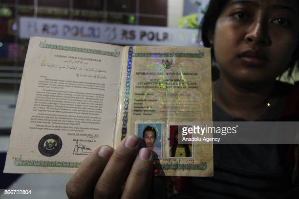 A wife of a victim of the explosion at a fireworks factory shows her marriage license at the Police Forensic Hospital in Kramatjati subdistrict of...
