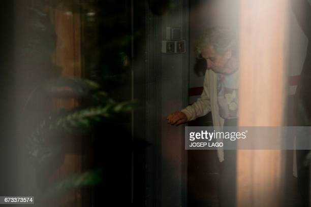 Wife of Catalan former regional President Jordi Pujol Marta Ferrusola walks through a doorway in her residence building where Spanish police carried...