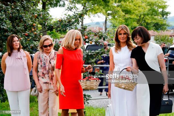 Wife of French President Brigitte Macron and Japan's Prime Minister's wife Akie Abe hold a basket full of Espelette peppers as they stand next to...