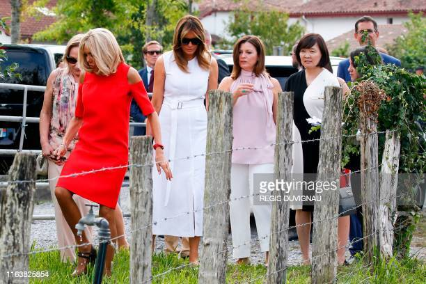 Wife of French President Brigitte Macron followed by US First Lady Melania Trump Australia's Prime Minister's wife Jenny Morrison Japan's Prime...
