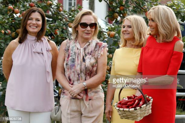 Wife of French President Brigitte Macron holds a basket full of Espelette peppers as she stands next to Australia's Prime Minister's wife Jenny...