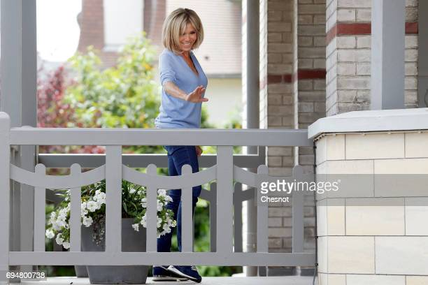 Wife of French President Emmanuel Macron Brigitte Trogneux gestures on the balcony of her house as her husband Emmanuel Macron leaves on June 11 2017...
