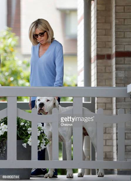 Wife of French President Emmanuel Macron Brigitte Trogneux is seen on the balcony of her house with her dog as her husband Emmanuel Macron leaves on...