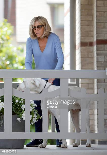 Wife of French President Emmanuel Macron, Brigitte Trogneux is seen on the balcony of her house with her dog as her husband Emmanuel Macron leaves on...