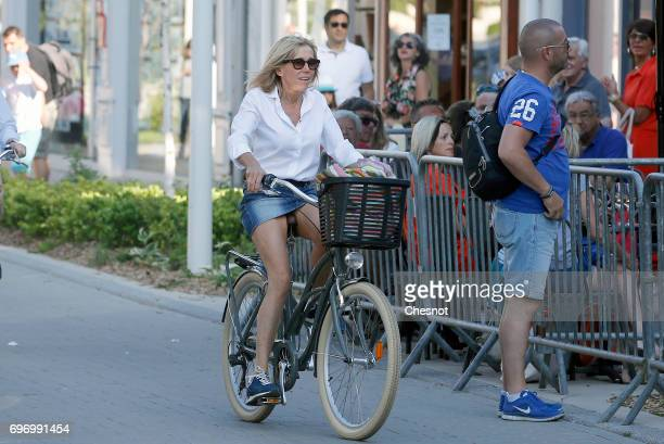 Wife of French President Emmanuel Macron Brigitte Trogneux returns to her home on a bicycle the eve of the second round of the French parliamentary...