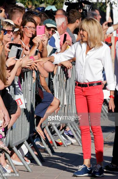 Wife of French President Emmanuel Macron Brigitte Trogneux shakes hands as she leaves her home the eve of the second round of the French...