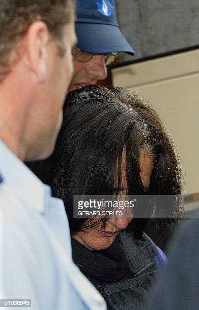 Wife of French serial killer Michel Fourniret Monique Olivier is escorted by police as she arrives 07 July 2004 for a hearing at Dinant police...