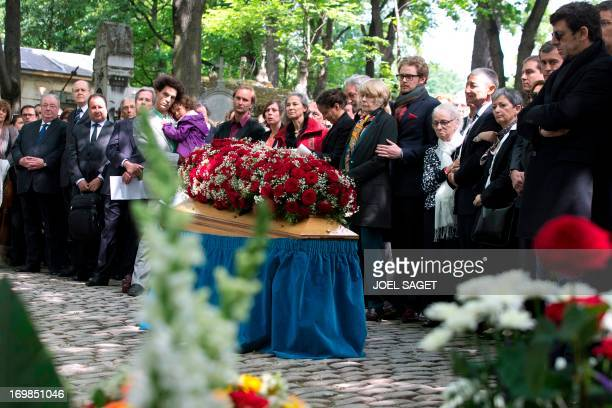 Wife of late Guy Carcassonne Claire Bretecher and French singer Patrick Bruel stand on June 3 2013 at the Montmartre cemetery in Paris during the...