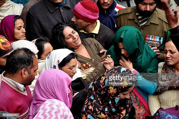 Wife of martyr Sanjeevan Singh Rana who was killed in terrorist attack in Pathankot wails near his body during his funeral at his native village...