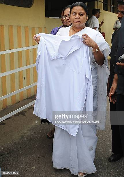 Wife of Sri Lanka's jailed exarmy chief Sarath Fonseka Anoma Fonseka displays the clothes worn by her husband at the time of being taken to jail...