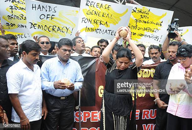 Wife of Sri Lanka's jailed exmilitary chief Sarath Fonseka Anoma Fonseka dashs a coconut on the ground during a protest with opposition lawyers...