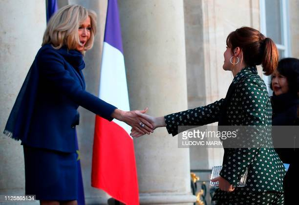 Wife of the French President Brigitte Macron shakes hands as she welcomes British actress Emma Watson to The Elysee Palace in Paris on February 19...