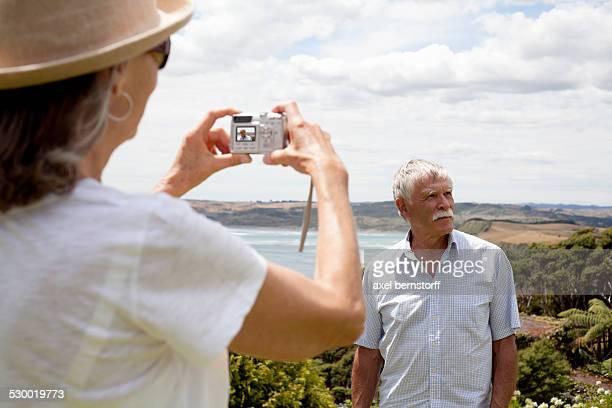 Wife photographing husband, ocean in background, Raglan, New Zealand