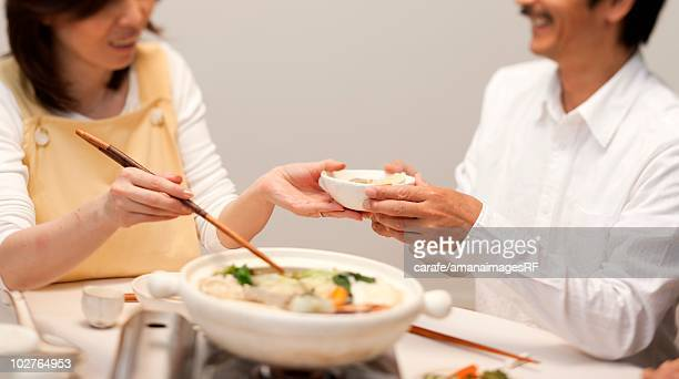 Wife serving food for her husband at dinner table