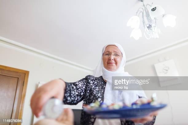 femme au service de son mari nourriture douce et de cologne pour eid al-fitr (fin du ramadan) - bonne fete de ramadan photos et images de collection