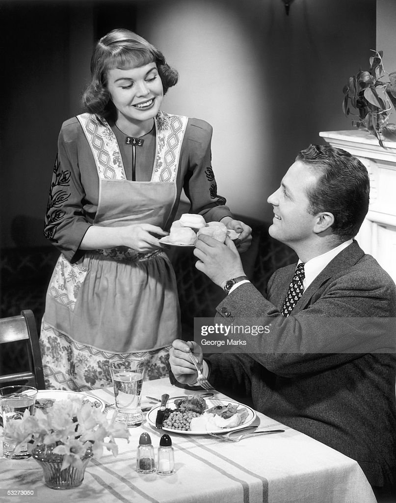 Wife serving husband dinner : Stock Photo
