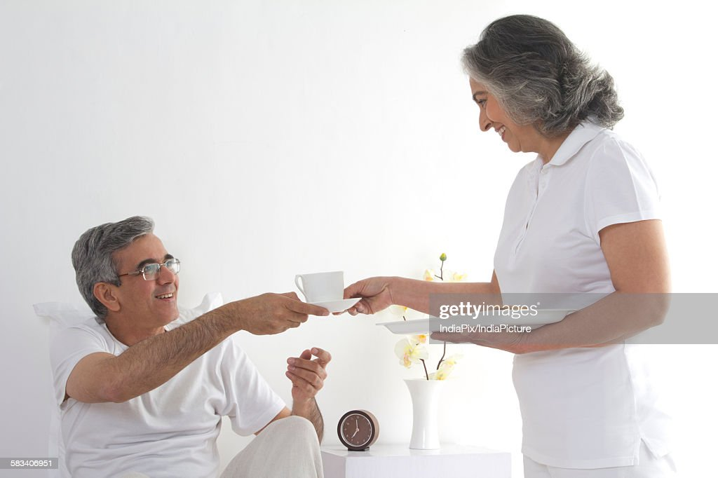 Wife serving tea to her husband : Stock Photo