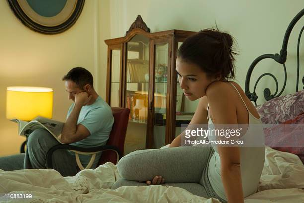 wife sitting on bed alone in thought, husband reading in background - sexual issues stock pictures, royalty-free photos & images