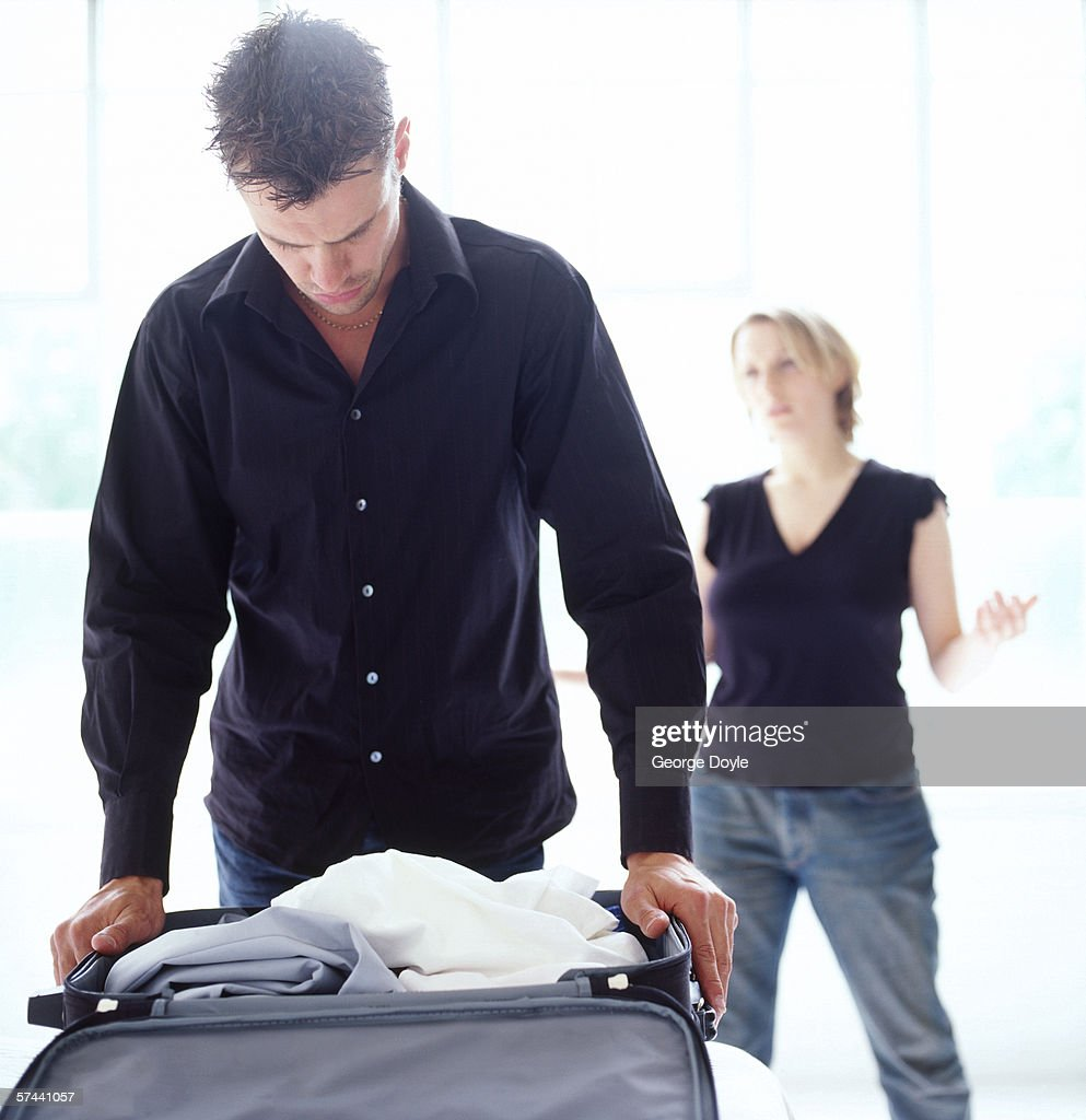 wife talking to her husband who is packing his suitcase : Stock Photo