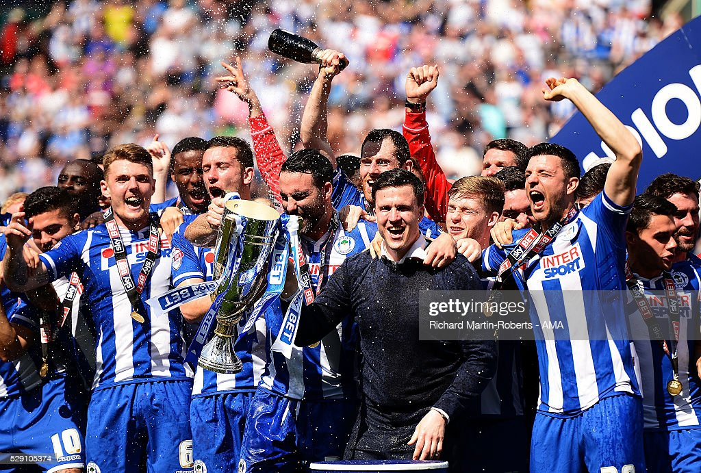 Wigan Athletic Manager Gary Caldwell lifts the Sky Bet League One trophy as his players celebrate winning the 2015/16 Sky Bet League One Championship at the end of the Sky Bet League One match between Wigan Athletic and Barnsley at DW Stadium on May 8, 2016 in Wigan, England.